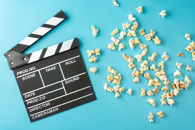 Movie clapperboard and popcorn on blue