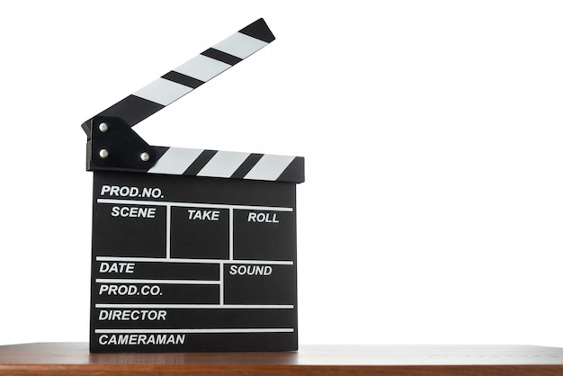 Movie clapperboard on table on white isolated space