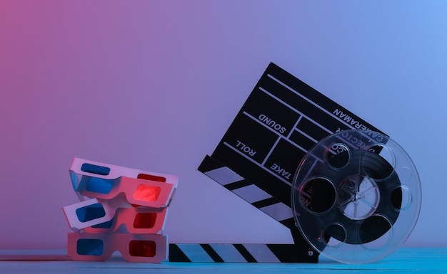 С 'хлопушкой' фильма с катушкой пленки и 3d-очками в красном синем неоновом свете. развлекательная индустрия