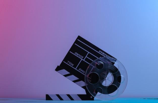 С 'хлопушкой' фильма с катушкой пленки в красном синем неоновом свете. развлекательная индустрия