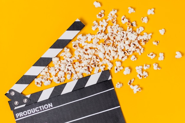 Movie clapperboard with popcorns on yellow background