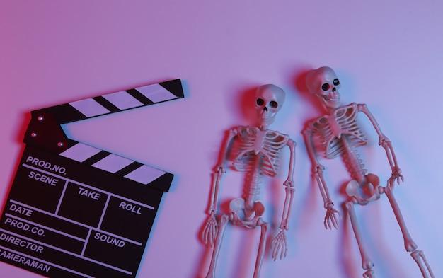 グラデーションネオン赤青光のスケルトンと映画のカチンコ。ハロウィン怖い映画