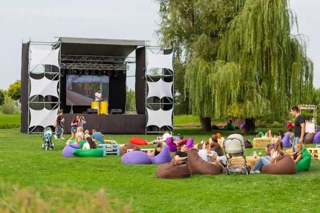 Movie day. people watch a movie on the street on a large screen, sitting on a green lawn and in comfortable bags