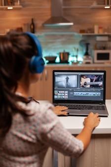 ポストプロダクション用の最新のソフトウェアを使用して映画を編集するムービーメーカー。深夜に編集するための最新のソフトウェアを使用して映画のモンタージュに取り組んでいる在宅勤務のコンテンツ作成者。