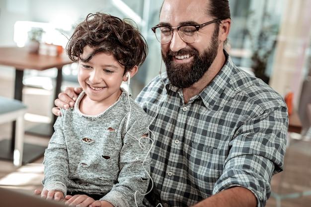 Фильм на ноутбуке. сияющие счастливые отец и сын смотрят фильм на ноутбуке, деля наушники