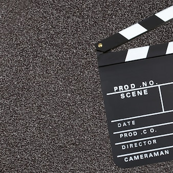 Movie production clapper board over dark background with copy sp