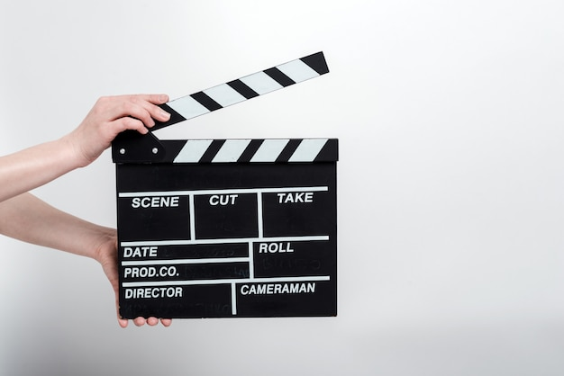 Movie production clapper board in the female hands against a white wall