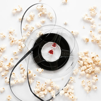 Movie reel and popcorn on white background