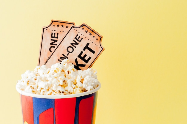 Movie tickets, film strips and popcorn on blue