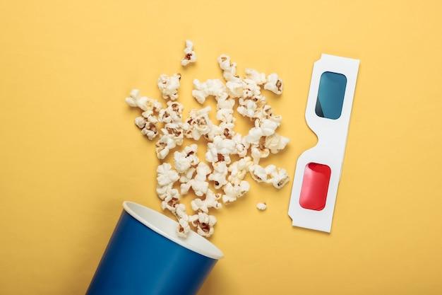 映画の時間。ポップコーンの段ボールのバケツと黄色の表面に立体アナグリフ使い捨て紙3dメガネ。上面図