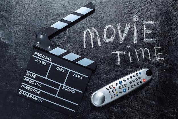 Время кино. доска с хлопушкой фильма и пульт от телевизора на доске мела.