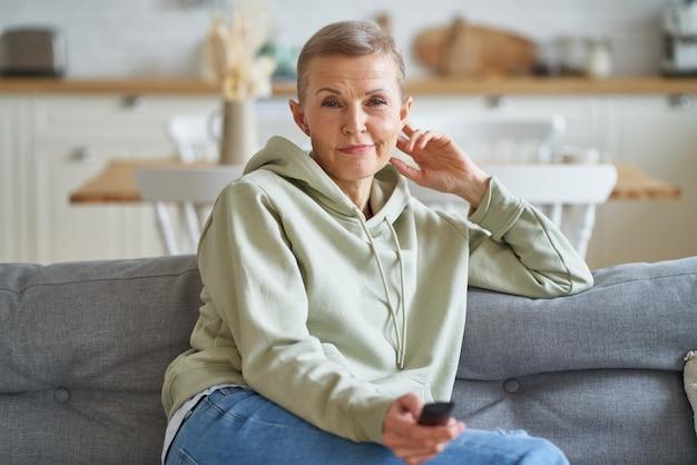 Время кино портрет красивой женщины средних лет с пультом дистанционного управления в руке, смотрящей телевизор во время просмотра телевизора