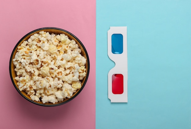 Movie time. stereoscopic anaglyph disposable paper 3d glasses and popcorn on blue pink pastel background. top view