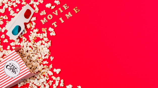 Movie time text with 3d glasses and spilled popcorn on red background