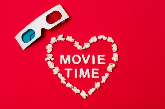 Movie time written in heart shape with 3d glasses on red background