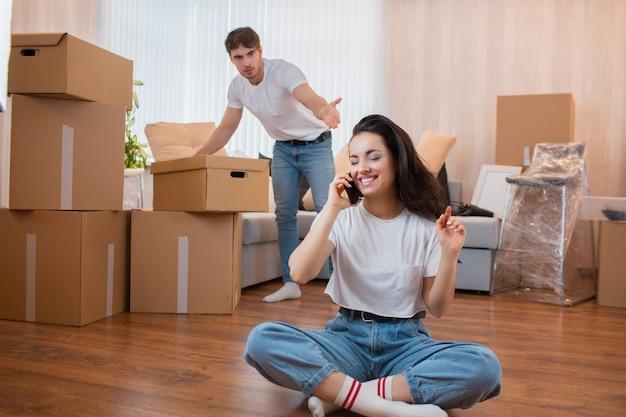 Перемещение и концепция отношений. он не удовлетворен. муж распаковывает коробки Premium Фотографии