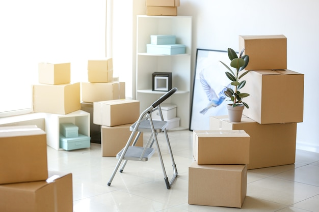 Moving boxes with belongings in room
