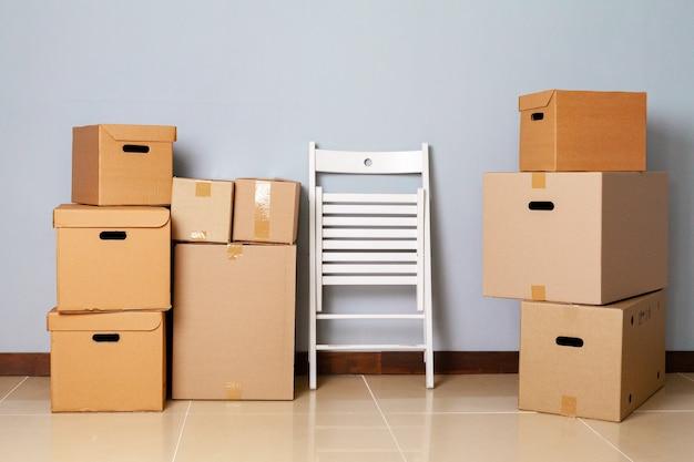 Коробки с упакованными вещами и стул для переезда