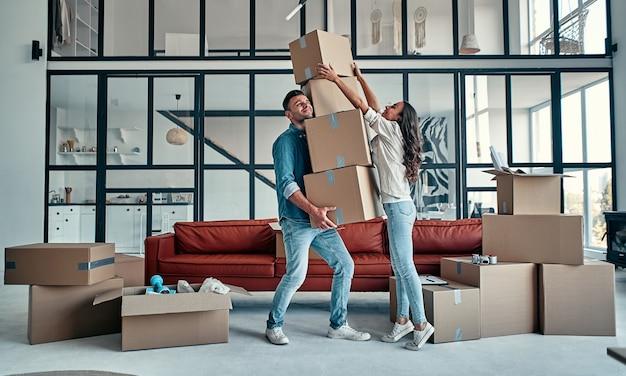 Переезд, покупка дома, концепция квартиры. молодая пара с кучей падающих коробок смешно пытается их поймать.