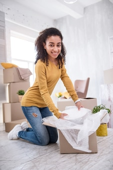 Moving in. charming young girl standing on her knees on the floor and smiling at the camera while taking plates out of the box