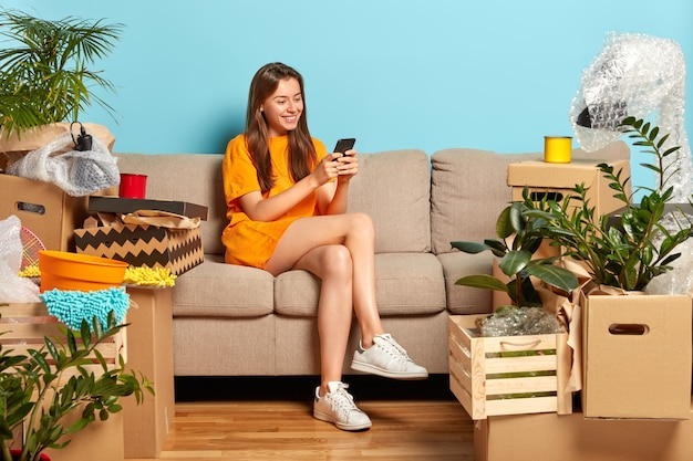 Moving concept. cheerful young female model surrounded with lot of boxes