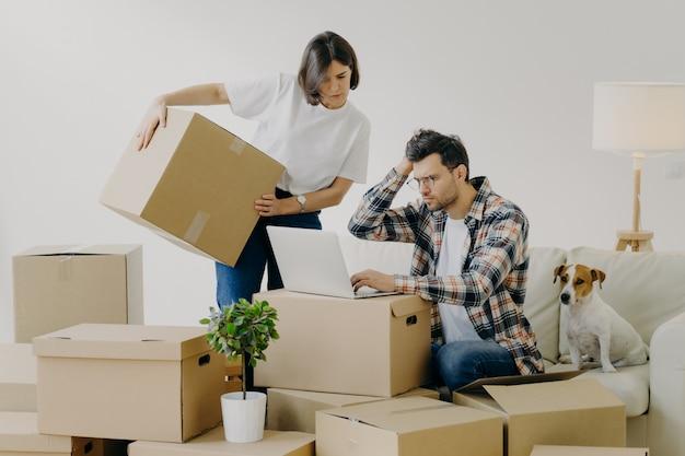 움직이는 개념. 좌절 된 젊은 남자가 온라인으로 필요한 정보를 검색하기 위해 현대 노트북 컴퓨터를 사용하고, 여자는 개인 소지품으로 큰 판지 상자를 대체합니다. 새로운 가정과 생활 개념