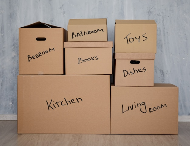 Moving day concept - stack of brown cardboard boxes with domestic things over gray wall background