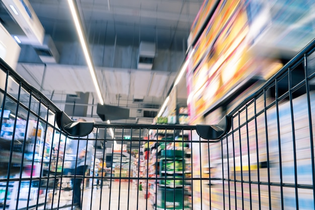 Moving empty black shopping cart with motion in the supermarket aisle, product on market s