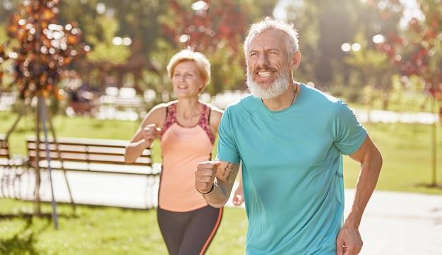 앞으로 함께 달리는 동안 집중된 스포츠웨어를 입고 활동적인 성숙한 가족 커플을 이동합니다.