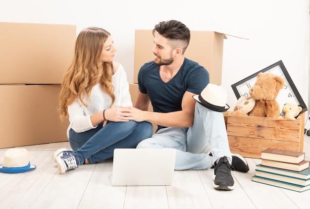 Переезд домой. пара сидит на полу в новом доме крупным планом