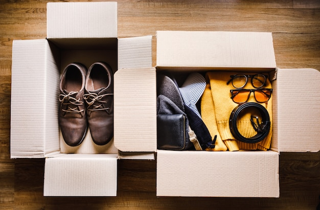 Moving home and donation concepts with accessories clothing in brown box.