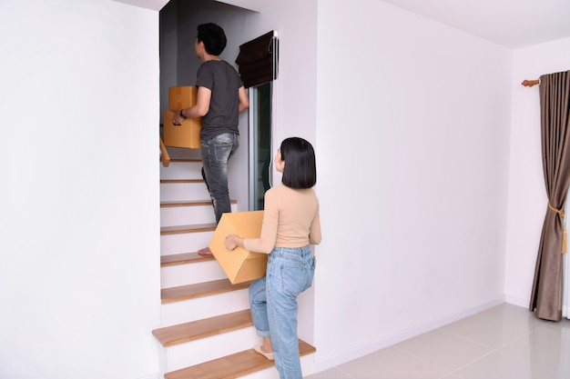 Moving house concept. young asian women are holding their stuff in a paper box.