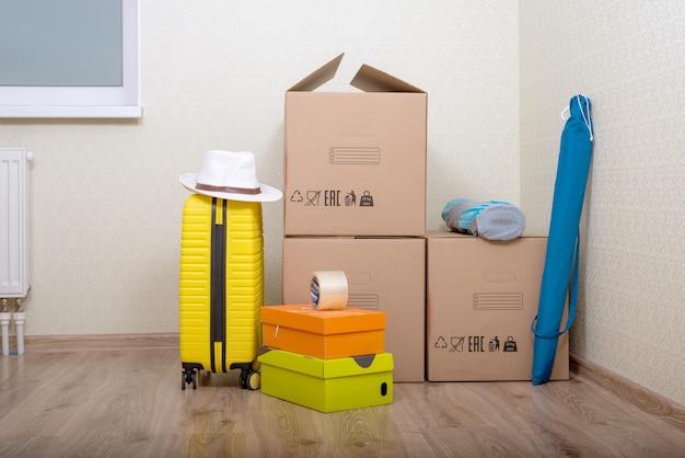 Переезд с картонными коробками и чемоданом