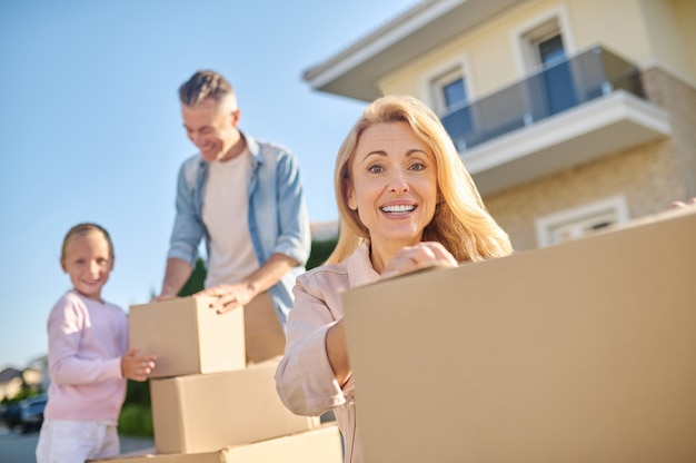 Moving, mood. pretty woman with toothy smile crouched near boxes and man with girl standing near things at distance on street