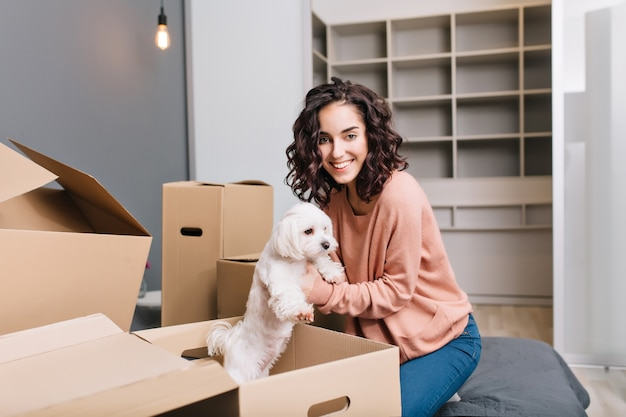 Moving to new modern apartment of joyful young woman finding a little white dog in carton box. smiling of beautiful model with short curly brunette hair at home comfort