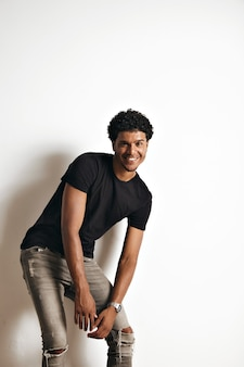 Moving playful athletic black model with an afro wearing a blank black t-shirt and grey skinny jeans on white wall