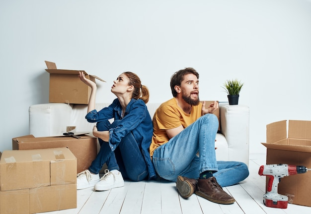 Moving renovation happy man and woman on the floor in a new apartment with boxes.