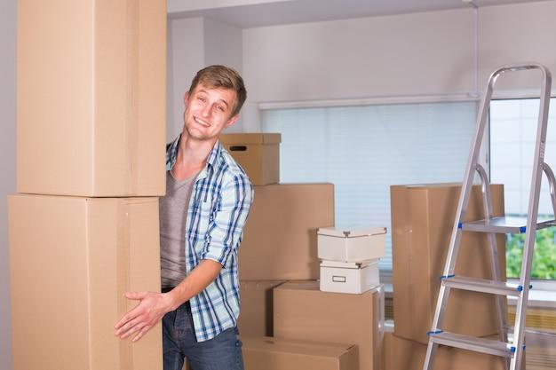 Переезд в новую квартиру. веселый молодой человек держит картонные коробки и улыбается в камеру во время
