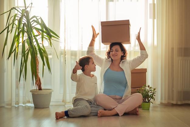 段ボール箱で新しい家の家族の母と息子に移動