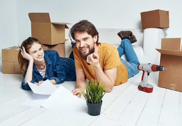 При переезде в квартиру мужчина и женщина лежат на полу, а цветок в горшке.