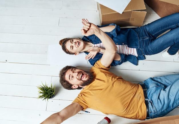 Переезжая в квартиру, мужчина и женщина лежат на полу, а цветок в горшке.