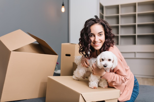 小さな犬と一緒に若いきれいな女性の新しいアパートに移動します。ベッドの上で身も凍るように、ペットと一緒にカートンボックスを囲み、笑顔で、積極性を表現する