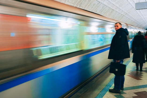 Moving train on the platform in the metro of moscow and people