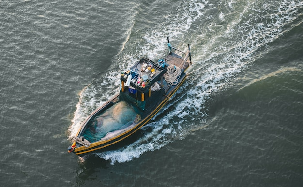 바다에서 나무 어업 보트를 이동합니다.