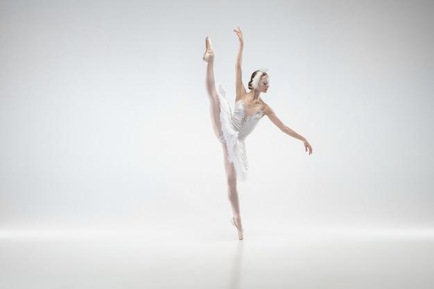 引っ越し。白いスタジオの背景に踊る若い優雅な古典的なバレリーナ。白鳥のような優しい服を着た女性。優雅さ、芸術家、動き、行動、動きの概念。無重力に見えます。