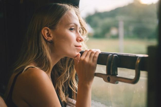 Настроение атмосферный образ жизни портрет девушки молодые красивые светлые волосы, глядя в окно от поезд. довольно предназначенное для подростков наслаждаясь красотой природы от moving вагона в лете.