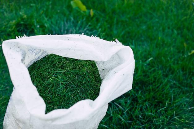 仕事の後に大きな白いバッグに芝生から草を刈った