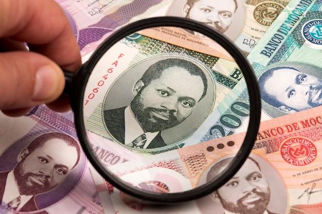 Мозамбикский метикал в увеличительном стекле на фоне бизнеса