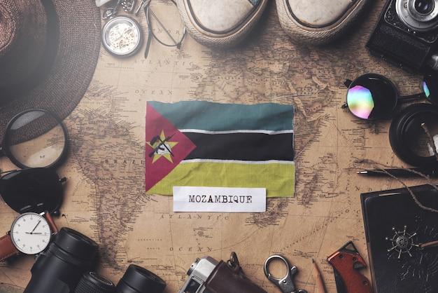 Флаг мозамбика между аксессуарами путешественника на старой винтажной карте. верхний выстрел