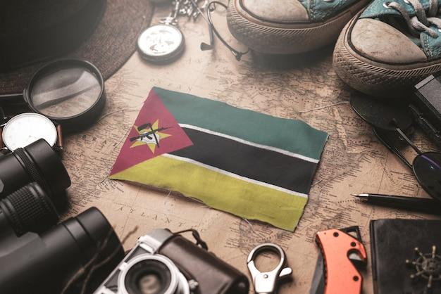 Флаг мозамбика между аксессуарами путешественника на старой винтажной карте. концепция туристического направления.